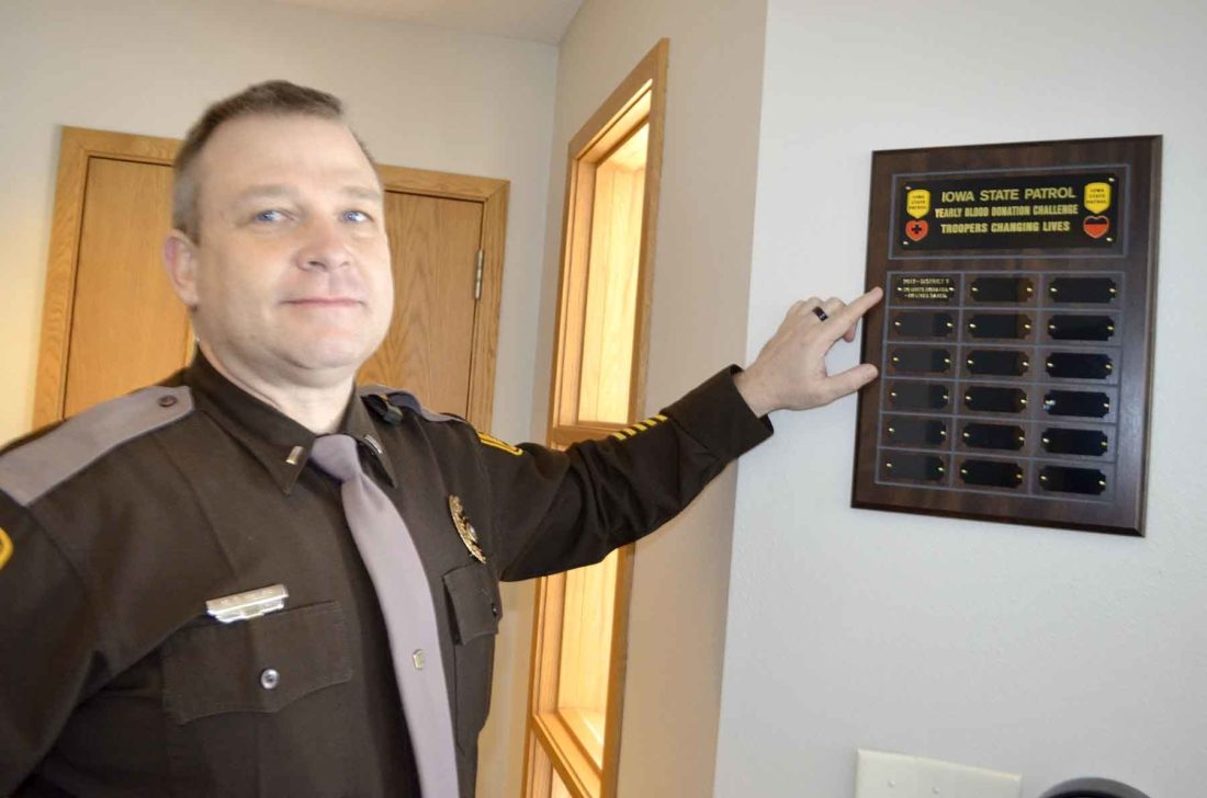 -Messenger photo by Peter Kaspari  Lt. Mark Miller, of the Iowa State Patrol, points to a plaque showing the Iowa State Patrol had the most blood donations of all state patrol districts during a recent blood drive.