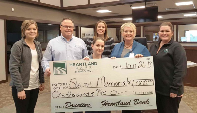 Heartland Bank recently donated $1,000 to Stewart Memorial Community Hospital and McCrary Rost Clinic to help with needed updates to the clinic for handicap accessibility to the exam rooms and patient restrooms.  Pictured from left are Bre Ahrens, Heartland Bank personal banker; Kevin Black, Heartland Bank president and CEO; Dr. Margaret Vitiritto, McCrary Rost Clinic; Mary Ludwig, director of marketing for SMCH; and Ashley Hanlon, Heartland Bank loan admin clerk. Mindy Roper, Heartland Bank personal banker, is in back.