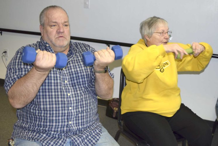-Messenger photo by Peter Kaspari  Doug Mueller, left, of Lehigh, lifts weights as instructor Mary Jane Lavender, of Fort Dodge, leads her exercise class Wednesday at Citizens Central.