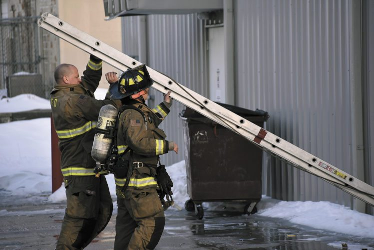-Messenger photo by  Chad Thompson   Fort Dodge firefighters Nathan Conrad, left, and Meghan Spears, set up a ladder outside of the Family Dollar store Wednesday afternoon.