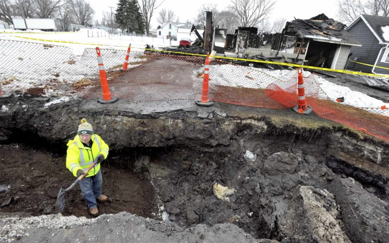 -Messenger photo by Hans Madsen  Jim Nelson, a location supervisor with United States Infrastructure Corporation, looks for the severed gasline in the hole City of Fort Dodge workers were repairing a water main in yesterday before a house explosion at 3015 Ninth Ave. S.