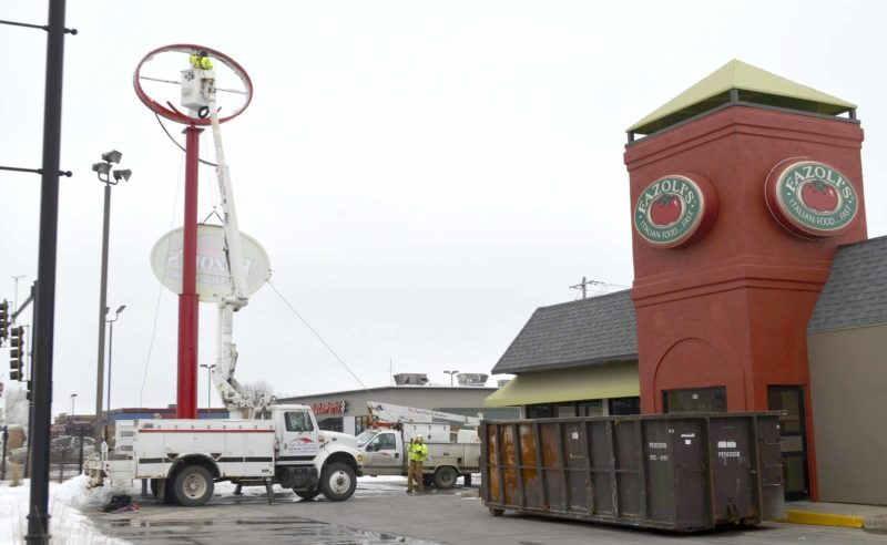 -Messenger photo by Joe Sutter  Crews lower the Fazoli's sign after unfastening it from its post along Fifth Avenue South. The store is closed, workers at the store confirmed Thursday. Items were being loaded into a large yellow moving truck on the other side of the building.