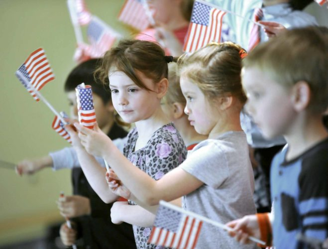 """-Messenger photo by Hans Madsen  Bianca Dougglas, 4, watches as her classmate, Zoe Stevens, 5, watches as her classmate, Bianca Dougglas, 4, unfurls her flag as they perform """"You're a Grand Old Flag"""" during the 2018 Patriotic Program at Community Christian School Friday afternoon."""