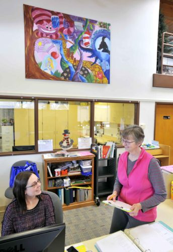 -Messenger photo by Hans Madsen  Manson Public Library Director Laura Koons, at right, stops to chat with Children's Librarian Nicole Oswald at the checkout desk. Behind them is a new painting by Manson Northwest Webster student Tiffany Espe that was recently added to the library. Student artist Andrea Lamphier also created a painting that is on display in the children's section.