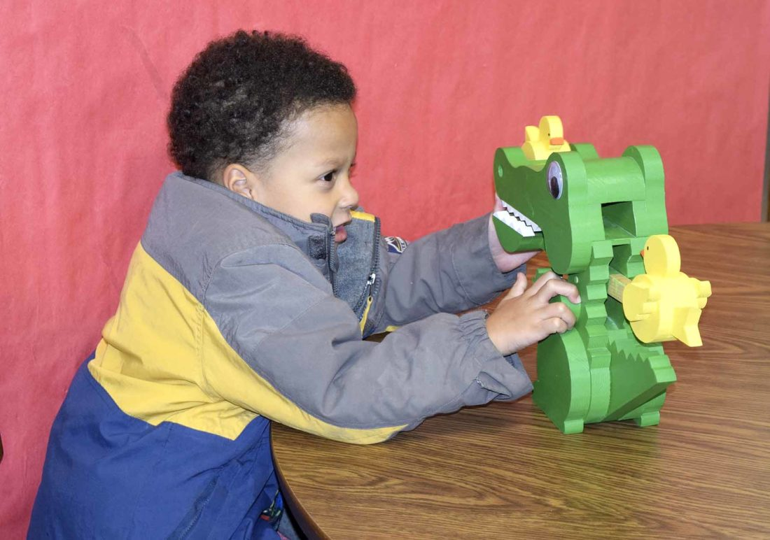 -Messenger photo by Peter Kaspari  Sebastian Guice-Mandel, 4, of Laurens, plays with a toy alligator at the Laurens Public Library. The library is in the process of raising money for a musical instrument garden that will be available for anyone to use.