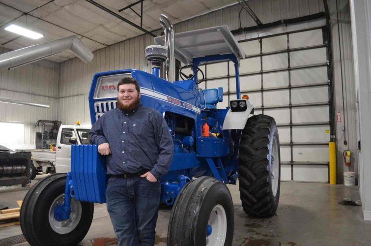 -Messenger photo by Kriss Nelson Nate Casady stands with the 1969 8000 Ford tractor he restored. Casady won grand champion honors with the tractor at the 2017 Iowa State Fair.