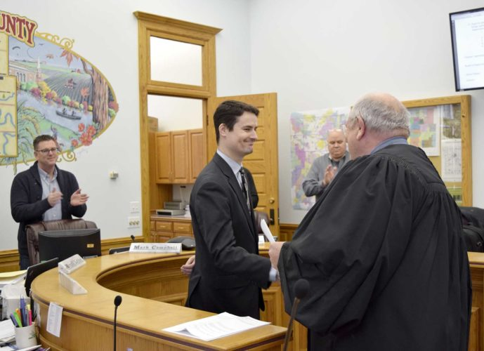 -Messenger photo by Joe Sutter  Darren Driscoll, left, shakes hands with Judge Thomas Bice after being sworn in as the new Webster County Attorney Tuesday morning. County Supervisors Mark Campbell, left, and Bob Thode applaud.