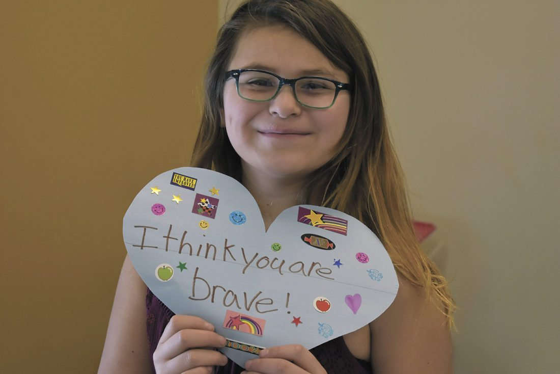 -Messenger photo by Chad Thompson  Maggie Pina-Hernandez, 11, a fifth-grader at Fort Dodge Middle School, holds up her heart-shaped card at the school Thursday morning.