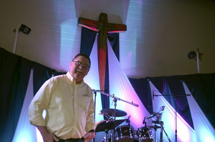 -Messenger photo by Peter Kaspari  The Rev. David Grindberg, senior pastor at St. Olaf Lutheran Church, poses inside the church on a stage where Wednesday night worship is held. Grindberg is leaving the church next week to become the pastor at First Lutheran Church in Algona.