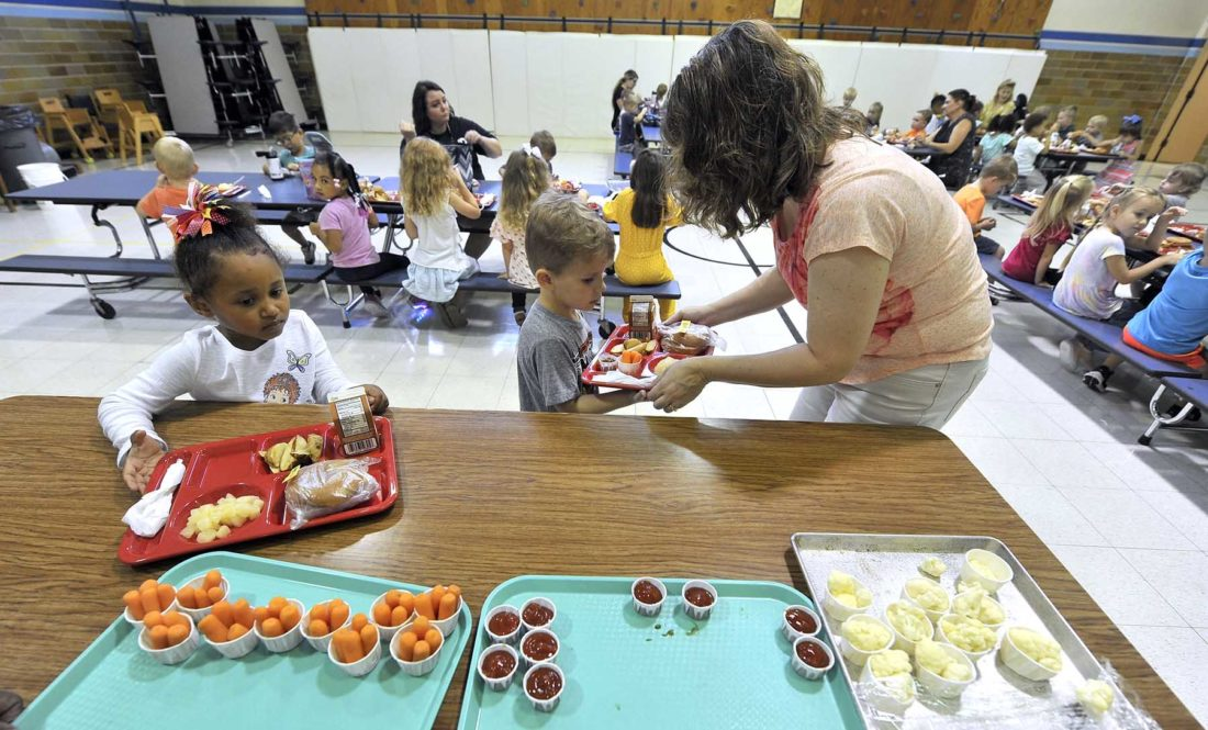 teacher helps child with lunch tray