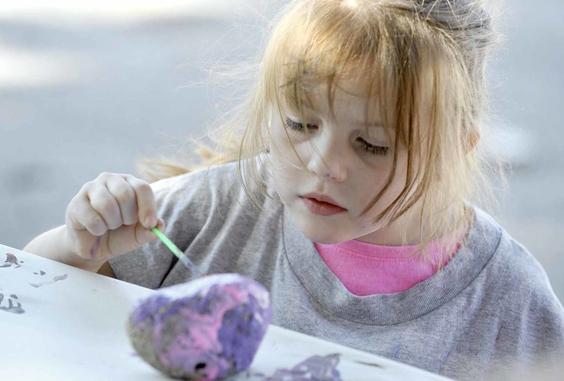 student painting a rock