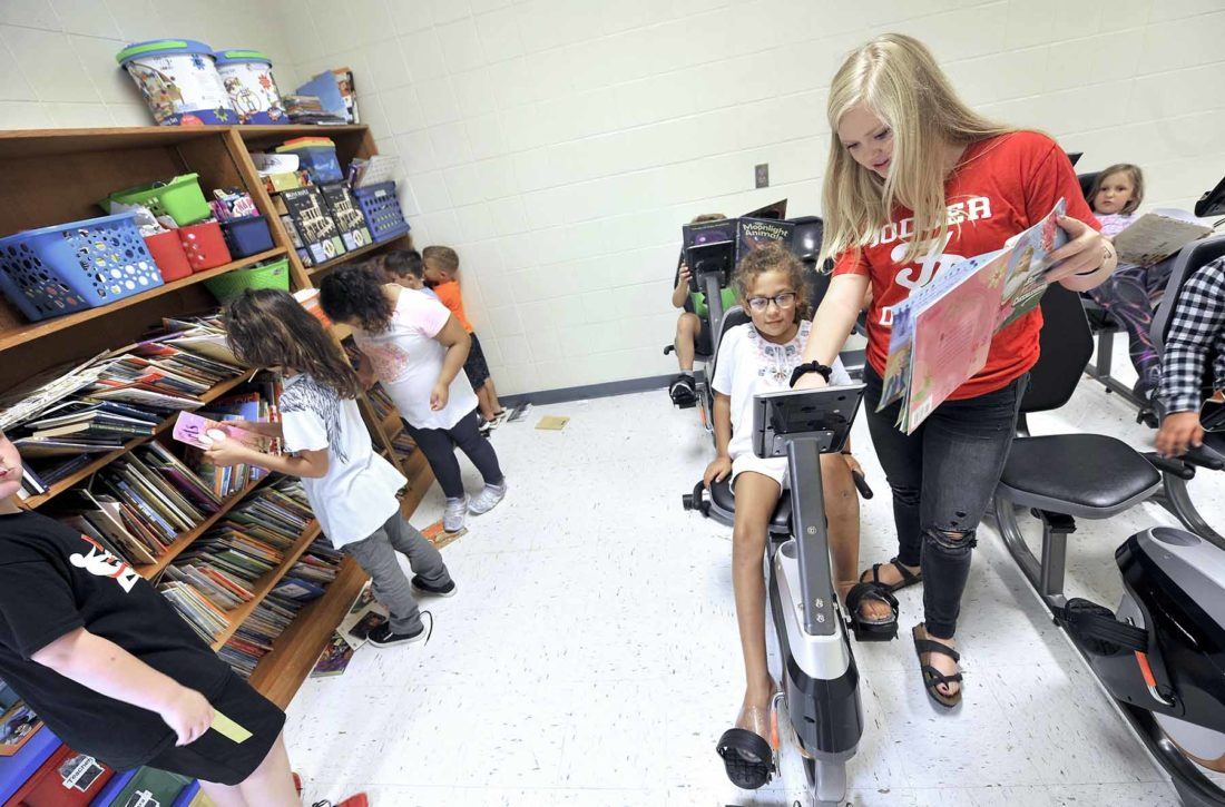 high school student helping elementary student set up stationary bike to read on