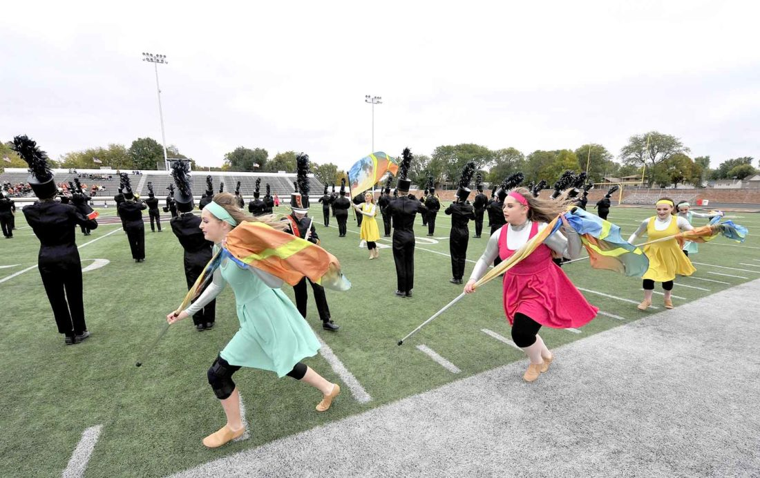 members of color guard run down sideline behind band