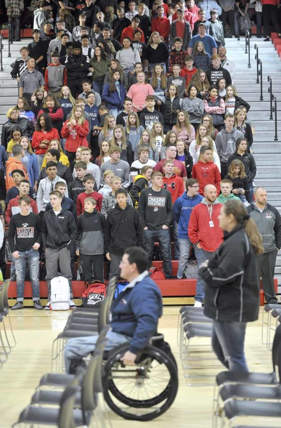 students stand as veterans enter gym