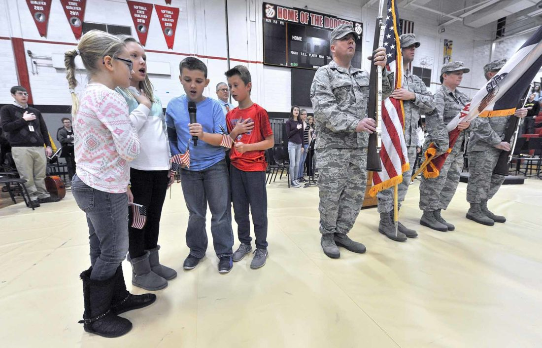 students lead the Pledge of Allegiance next to military members presenting the colors