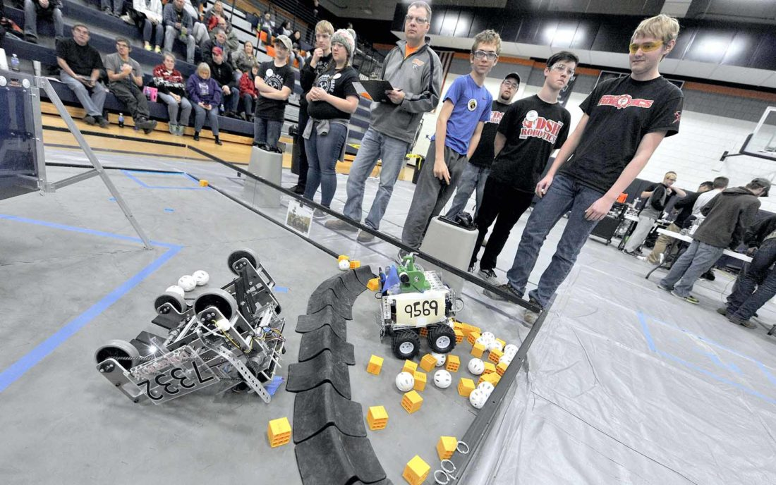 Robotics team members watch their robots during competition