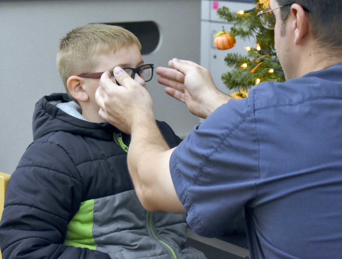 Vision to Learn staff member adjusts glasses on student's face