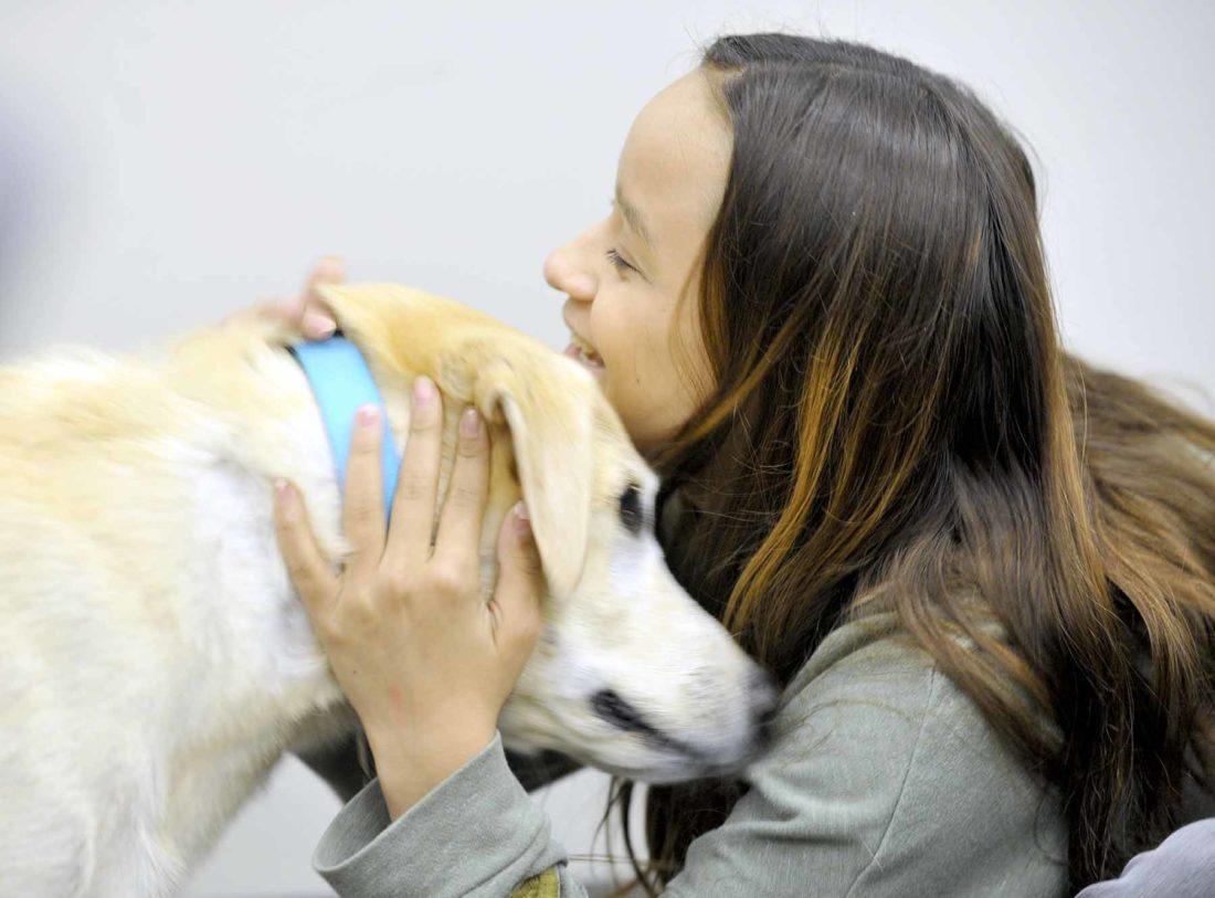 student hugs dog