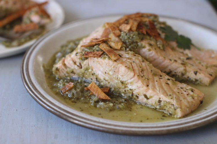 FILE -This Nov. 9, 2015, photo, shows salmon poached in green salsa and topped with baked chips in Concord, N.H. This dish is from a recipe by Sara Moulton. (AP Photo/Matthew Mead)