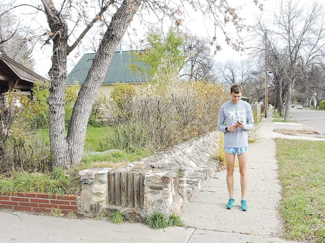 Kim Fundingsland/MDN  A jogger takes a break to check his cell phone on a beautiful fall day in Minot.