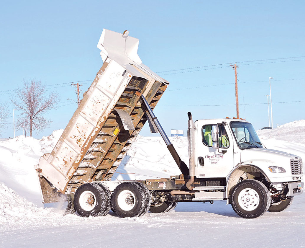 Kim Fundingsland/MDN A City of Minot truck dumps a load of snow at Sertoma Sports Complex parking lot on North Hill. The snow will be pushed into higher piles to make additional room if necessary.