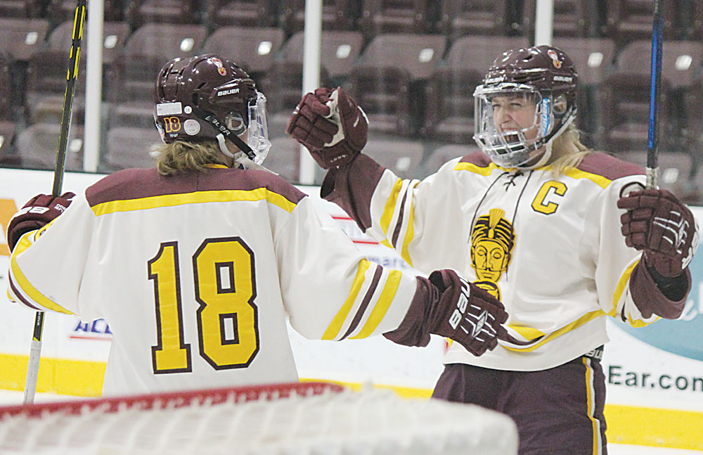 Alex Eisen/MDN Minot High senior MacKinzy MacIver celebrates with teammate Parker Larson (18) after MacIver scored the first goal of the game against the Grand Forks Knightriders Saturday afternoon at Maysa Arena.