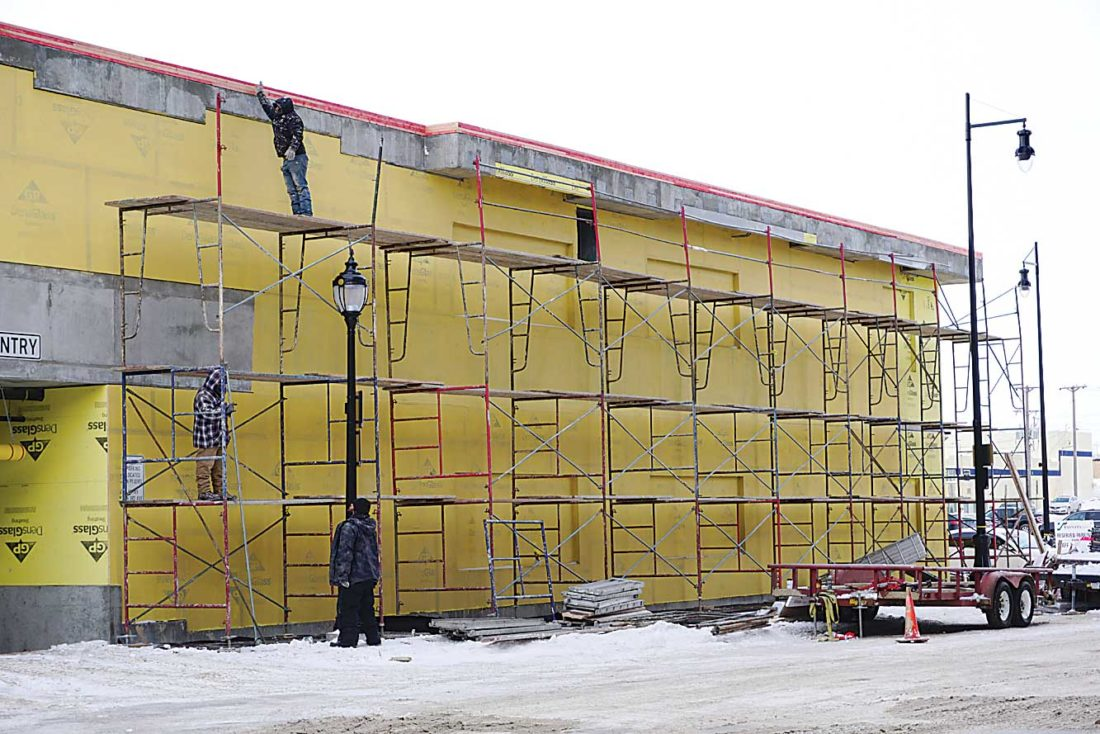 Jill Schramm/MDN Construction workers prepare to work on the exterior cladding on one of the two parking ramps in downtown Minot. The exterior finish on both downtown parking ramps is to be completed by Feb. 10 under a bid award granted by the Minot City Council to Rolac Contracting of Minot. Total cost is $573,6778 with contingencies and architectural/engineering expenses.