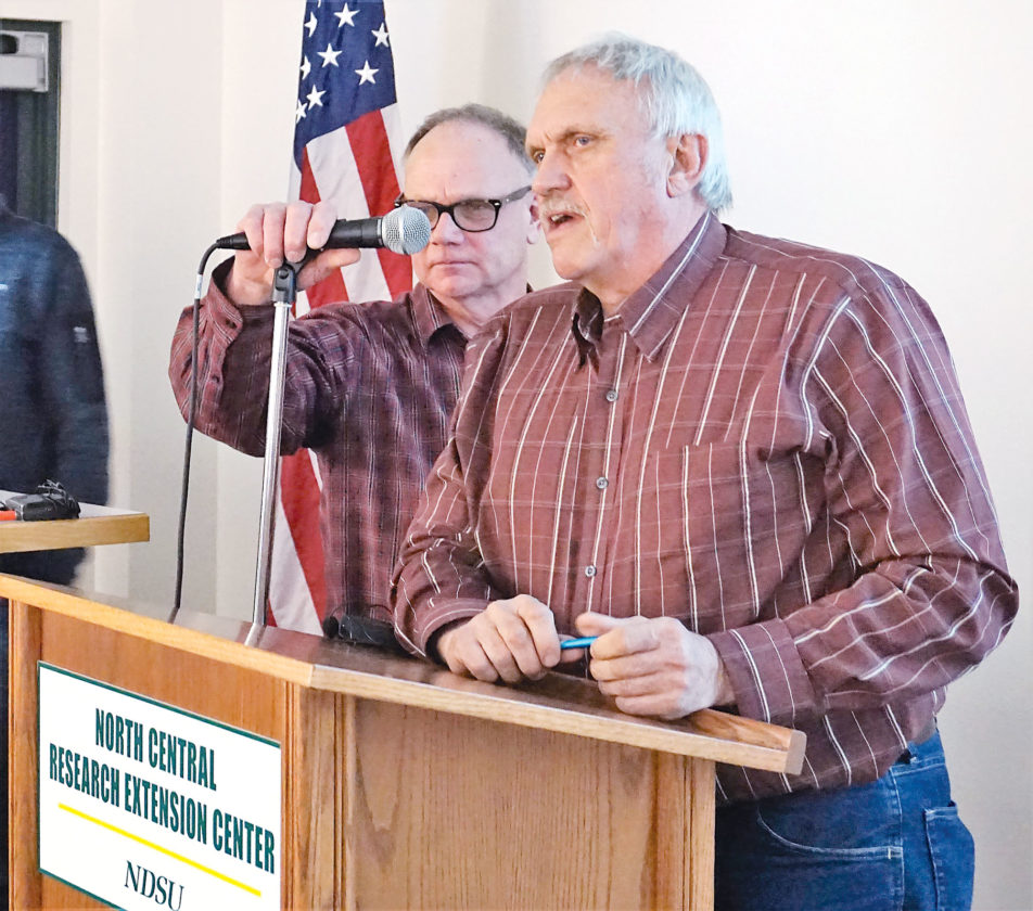 Jill Schramm/MDN Ward County Farm Bureau board member John Pietsch adjusts the microphone for Ward County Commission John Fjeldahl as he speaks to landowners at a Farm Bureau forum on right-of-way takings Wednesday at North Central Research Extension Center.