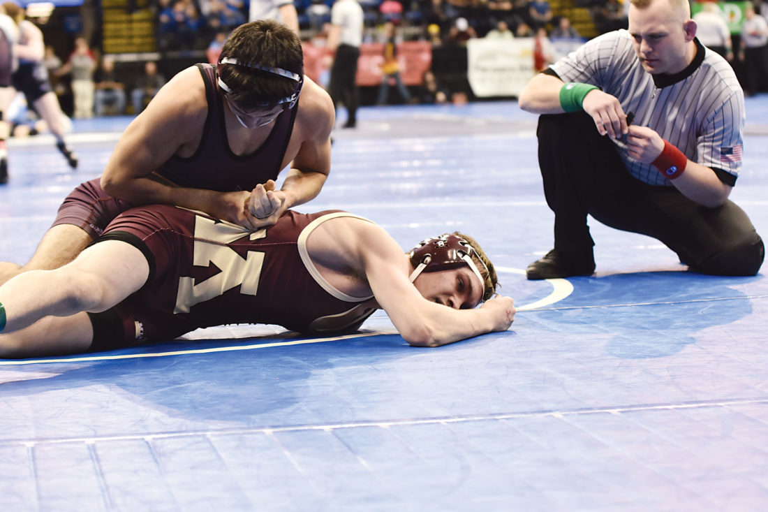 Garrick Hodge/MDN  Minot High's Tyler Strandberg, bottom, tries to escape the grasp of Grand Forks Red River's Gavyn Erickson, top, during the 132-pound quarterfinal matchup at the state wrestling tournament Thursday at the Fargodome.