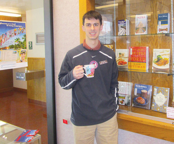 Allan Blanks/MDN Visitors are welcomed to sample foods from all over the world and enjoy a cup of tea with Brendan Chella, the adult services librarian at the Minot Public Library.