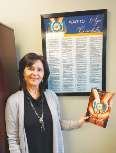 Jill Schramm/MDN  Terry Ferebee Eckmann holds a copy of her book while standing next to a poster listing 101 tips for aging gracefully.