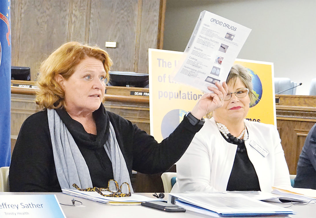 Jill Schramm/MDN Sen. Heidi Heitkamp holds a drug fact sheet from First District Health Unit as Renae Byre from the health unit looks on during a forum in Minot Thursday.