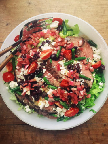 This March 2017 photo shows a Greek salad with flank steak in New York. This dish is from a recipe by Katie Workman. (Katie Workman via AP)