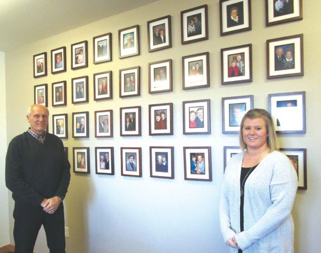Allan Blanks/MDN   Across the wall of Ken Kitzman's (to the left) office, are framed photographs of the hundreds of donors who have entrusted their gifts to the Minot Area Community Foundation. Each day, Staci Kenney, right, and members of the foundation are reminded of their responsibility to honor the visions of their donors.