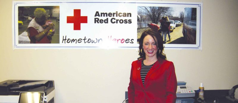 Andrea Johnson/MDN  Terri Philion, executive director of the Minot  chapter of the American Red Cross, poses by a sign in the Red Cross office on March 22.