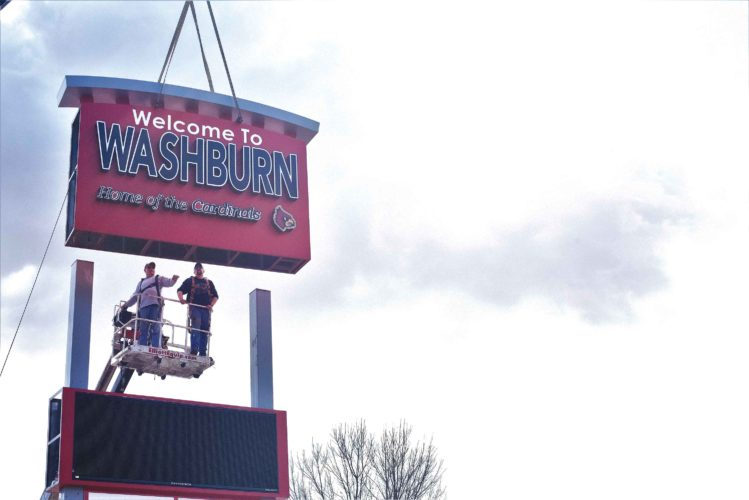 Submitted photo  Workers erect a digital community sign in Washburn. The recently erected sign was the project of the economic development group and a number of sponsors.
