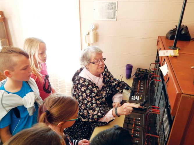 Submitted Photo   Each spring school children from throughout the region tour Prairie Village Museum. This group gets a lesson in how a telephone switchboard works from former operator Jan Norsby.