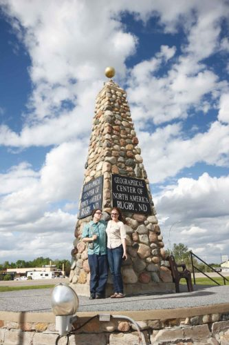 Submitted Photo  Visitors stop year round to take photos at the stone cairn marking the Geographical Center of North America in Rugby. Credit: Goodstorysarah.wordpress.com
