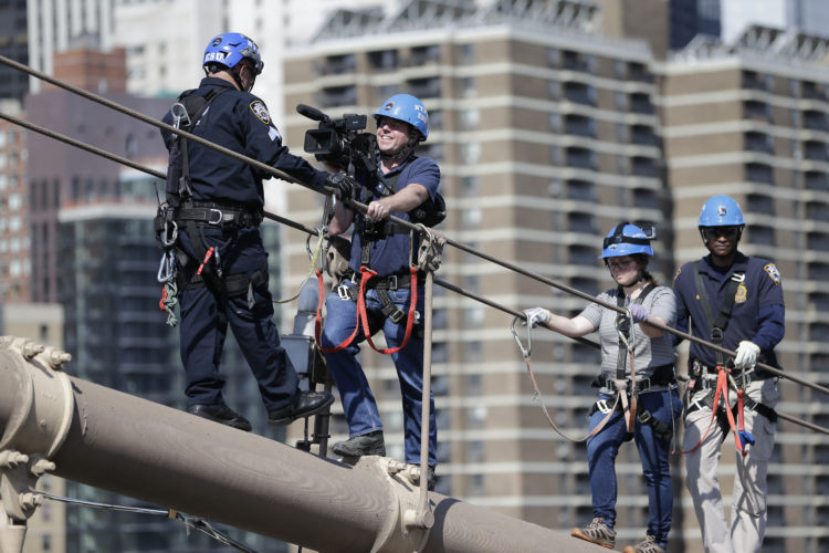 In this Tuesday, May 2, 2017, photo, a member of the New York Police Department's elite High Rise Rescue Unit, left, instructs Associated Press video journalist Ted Shaffrey, second from left, and AP reporter Colleen Long, second from right, during an exclusive demonstration scaling the Brooklyn Bridge for AP journalists in New York. The unit performs the most difficult rescues, including those on bridges and skyscrapers. (AP Photo/Seth Wenig)