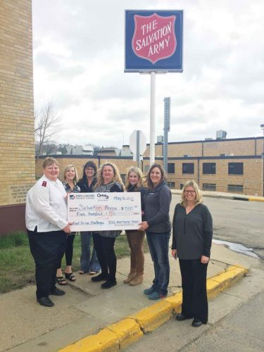 Submitted Photo Captain Debbie Stahl of the Salvation Army, left, Jane Mayer, Lisa Olson and Dorothy Martwick, all with Century 21 Action Realtors, Renata Buen, Jill Lohnes and Lisa Thuner, employees of Town & Country Credit Union, gather at a check presentation.