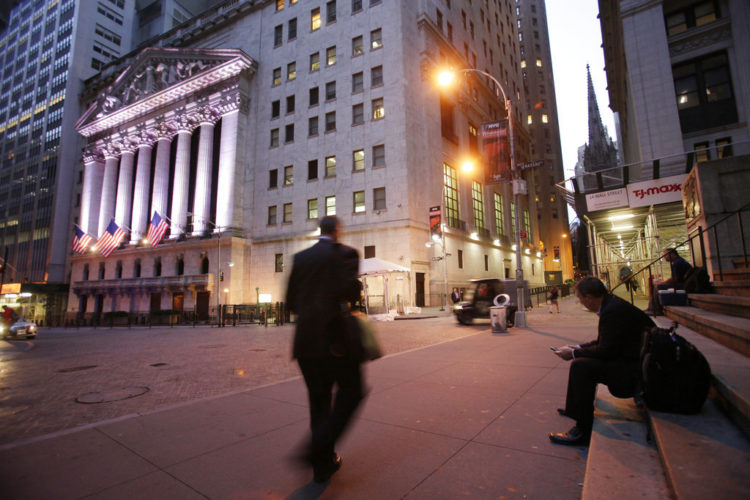 "In this Oct. 8, 2014, file photo, a man walks to work on Wall Street, near the New York Stock Exchange, in New York. Shares edged higher Monday, May 15, 2017, in Europe and Asia, despite worries of disruptions from the ""WannaCry"" ransomware cyberattack over the weekend. (AP Photo/Mark Lennihan, File)"
