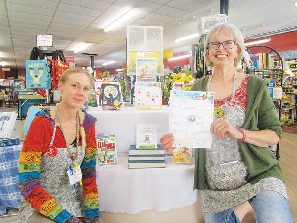 "Allan Blanks/MDN  Aly Stoeckley, left, manager, kneels beside owner Val Stadick, who holds a reading bingo card for the upcoming ""Summer Reading Kick-Off"" event hosted at Main Street Books, Saturday at 12 p.m."