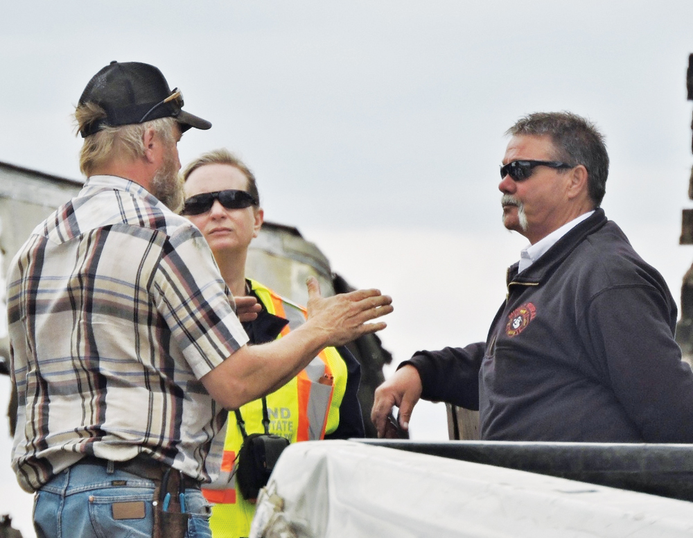 Kim Fundingsland/MDN Minot Rural Fire Department Chief Rex Welticol, right, conducts an interview at the scene of the Earth Recycling fire that occurred Thursday.