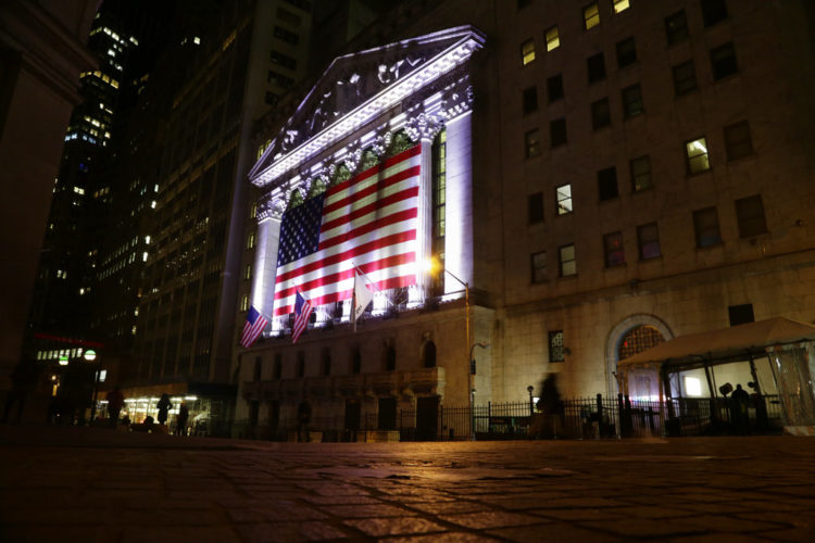 In this Friday, Feb. 17, 2017, file photo, an American flag hangs on the front of the New York Stock Exchange on an evening, in New York. Global stock markets traded in narrow ranges Wednesday, May 24, 2017, with investors brushing aside Moody's decision to cut China's debt rating. (AP Photo/Peter Morgan, File)