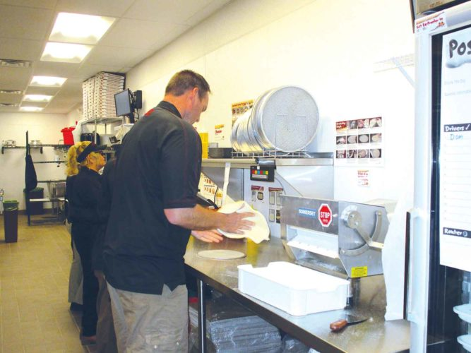 Allan Blanks/MDN Marco's Pizza owner Nathan Heinert prepares pizza dough as team members prep the sauce, cheese and toppings for a pizza order.