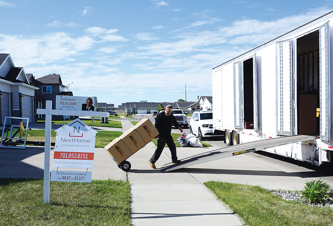 Jill Schramm/MDN A worker loads boxes into a moving van Wednesday in a southeast Minot neighborhood where a family is selling their home and relocating.