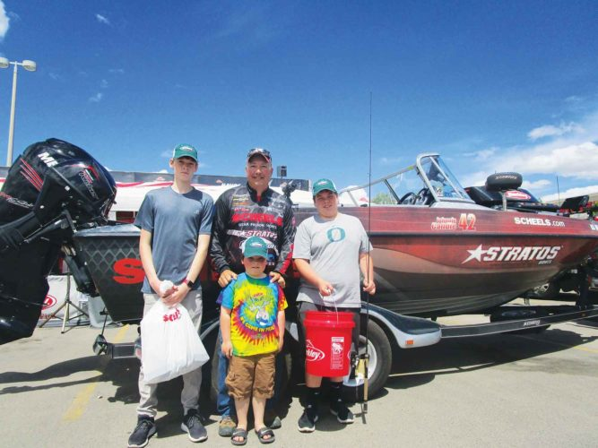 "Allan Blanks/MDN   Pro-fisherman and celebrity Johnnie Candleback center, stands besides Austyn Kraus, left, Kolby Begg, Damian Emly during ""Fish Fest"" at the Scheels in parking lot located at Dakota Square Mall, Thursday afternoon."