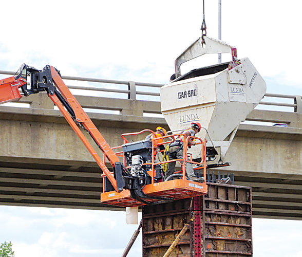 Jill Schramm/MDN Workers pour concrete into a form to create a pier for the east Broadway Bridge Thursday while traffic moves over the west bridge.