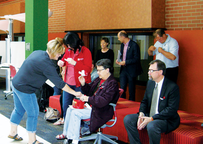 Andrea Johnson/MDN People attending a ceremony at Minot State University to mark Poppy Day tuck red poppies into their lapels on Friday.