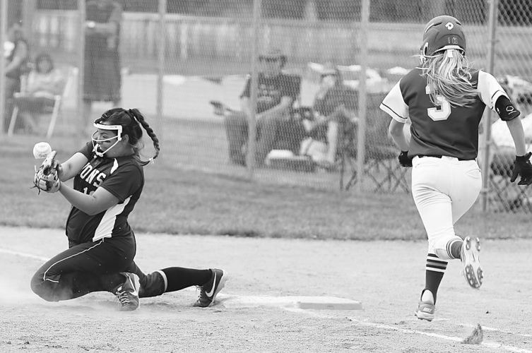 Photo courtesy of the Jamestown Sun Bishop Ryan first baseman Hannah Candrian tries to pick a low throw as Jamestown's Hannah Schiele runs down the first baseline during Saturday's West Region tournament game in Jamestown.